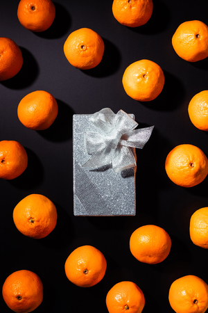 top view of fresh tangerines and silver gift box on black background