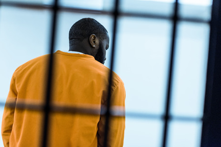 back view of african american prisoner behind prison bars Banco de Imagens