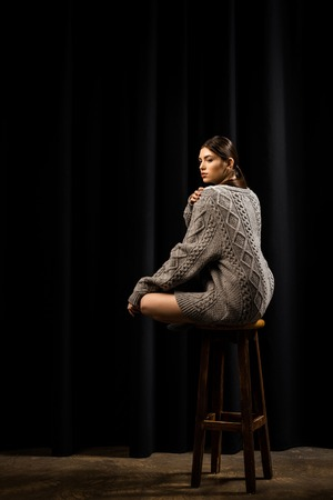 side view of young woman in woolen grey sweater sitting on wooden bar stool on black background Banque d'images - 111754136