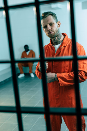 multiethnic criminals in prison cell behind prison bars Stock Photo