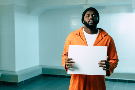 african american prisoner holding blank placard and looking at camera Stock Photo - 111754207