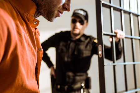cropped image of prison guard looking at criminal in prison cell Banco de Imagens