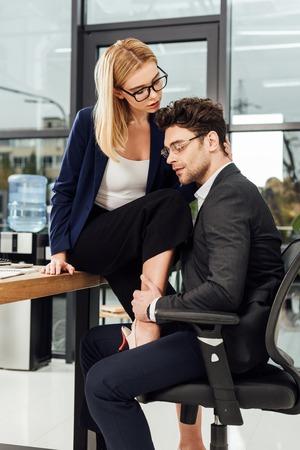 junge Geschäftsfrau flirtet mit Geschäftskollegen am Arbeitsplatz im Büro Standard-Bild