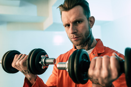 Tattooed prisoner training with dumbbells in prison room Stock Photo - 112273098