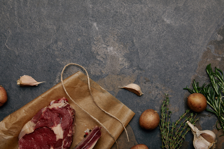 Top view of raw meat steak on baking paper with potatoes on grey background Stock Photo