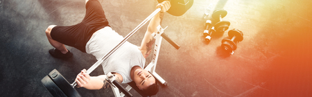 Muscular sportsman exercising with barbell at gym in sunlight Archivio Fotografico