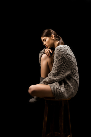 Side view of beautiful thoughtful woman in woolen grey sweater sitting on bar stool isolated on black Banque d'images - 112273074