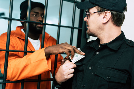 African american prisoner giving money to prison officer as bribe Banco de Imagens