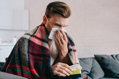 Sick young man sneezing with paper napkins sitting on couch