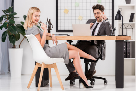 Young businesswoman looking at camera while flirting with business colleague at workplace with laptop in office Zdjęcie Seryjne