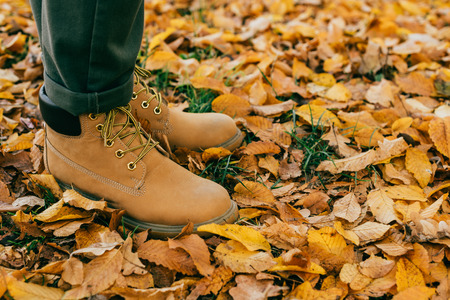 Cropped view of man in orange boots standing on colorful foliage