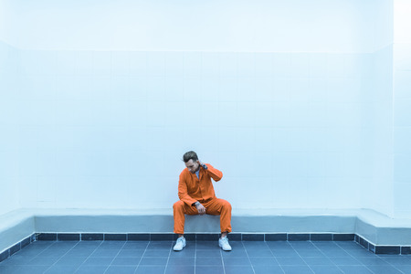 prisoner sitting on bench in prison cell