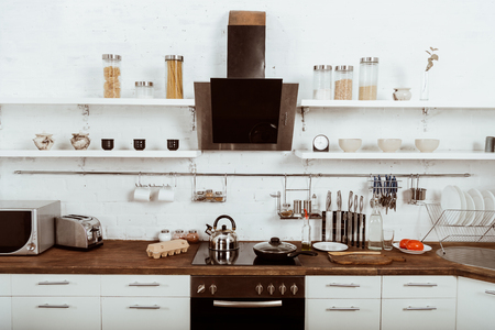 selective focus of modern kitchen interior with frying pan and teapot on stove 스톡 콘텐츠