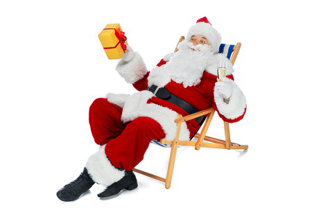 Santa Claus resting on beach chair with champagne glass and gift box isolated on white