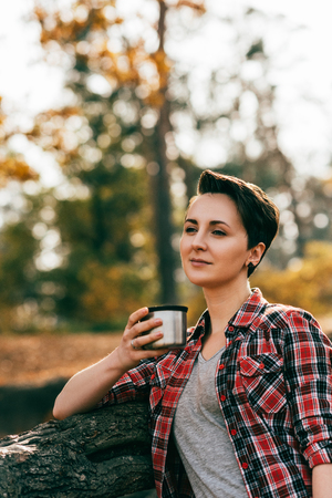 Adult woman holding metallic thermos cup on blurred autumnal background