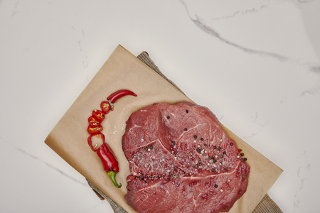 Top view of fresh raw meat on baking paper with chopped chili pepper on white background