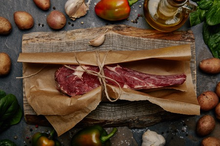 Raw rib eye steak wrapped in baking paper on wooden board with herbs, spices and potatoes Stock Photo