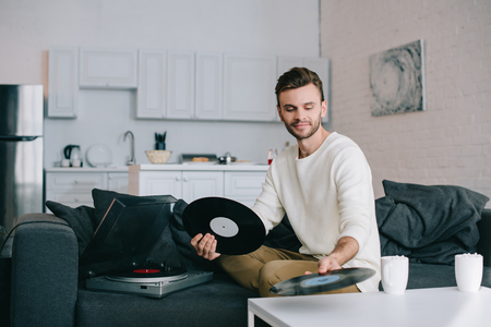 Attractive young man holding discs for vinyl record player while sitting on couch Archivio Fotografico