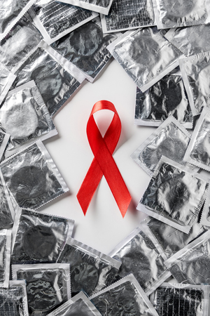 Top view of aids awareness red ribbon and silver condoms on white background Stockfoto