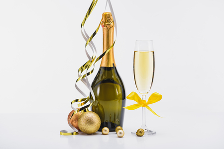 Close up view of bottle and glass of champagne, confetti and Christmas toys on white backdrop