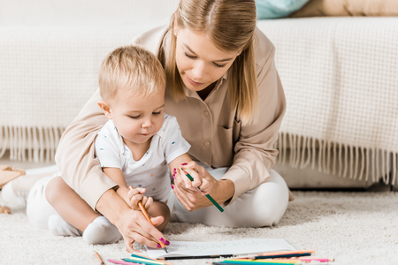 Mother and adorable toddler drawing together in nursery room