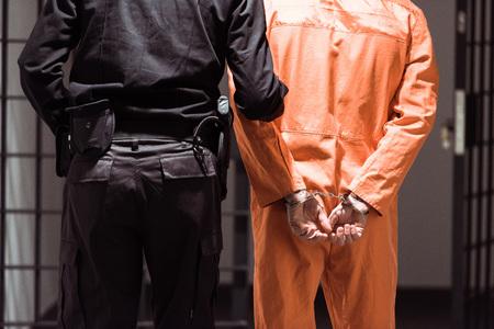 Vista trasera del oficial de prisiones líder preso esposado