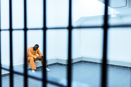 Afroamerykański więzień siedzący na ławce za kratami więziennymi