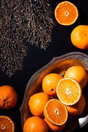 Flat lay with mandarins, decorative twig and metal bowl on black backdrop