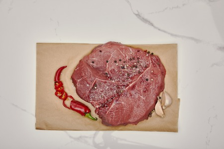 Top view of fresh raw meat on baking paper with chopped chili pepper and garlic on white background Stock Photo