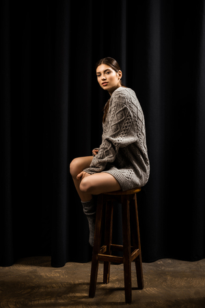 Young pretty woman in woolen grey sweater and socks on bar stool on black background Stock Photo