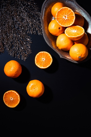 Flat lay with mandarins, decorative silver twig and metal bowl on black backdrop