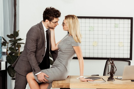 Side view of young business colleagues flirting at workplace in office Zdjęcie Seryjne