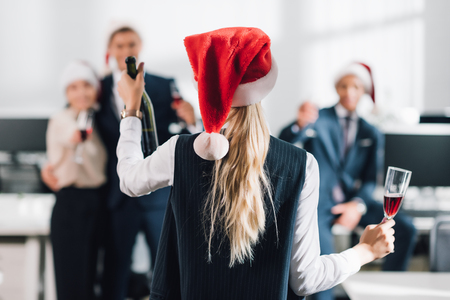 Back view of businesswoman in Santa hat holding glass and bottle of champagne while celebrating Christmas with colleagues Stock Photo
