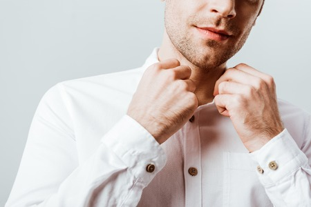 Cropped image of handsome businessman buttoning up white shirt isolated on grey Stock Photo