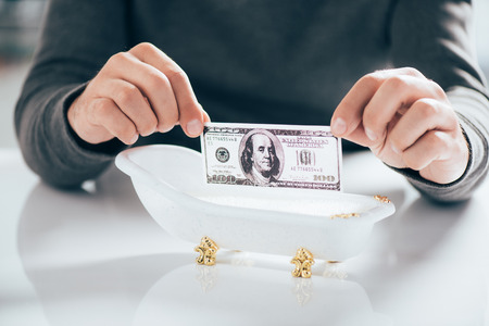 cropped shot of man holding dollar banknote above tub, money laundering concept 版權商用圖片