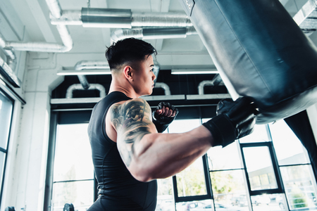 side view of young asian sportsman wearing boxing gloves and punching boxing bag at gym