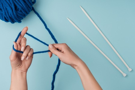 Partial view of woman with blue yarn and white knitting needles knitting on blue backdrop Reklamní fotografie - 112274430