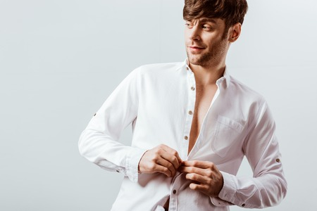Cheerful businessman buttoning up white shirt isolated on grey