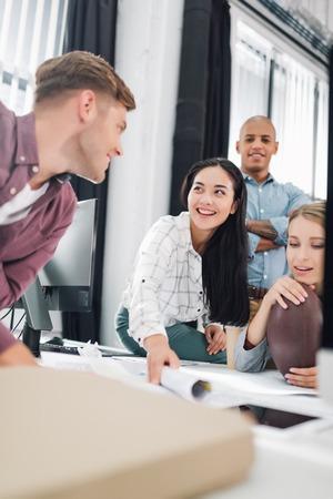 Jóvenes empresarios felices sonriendo mientras trabajan juntos en la oficina de espacios abiertos Foto de archivo