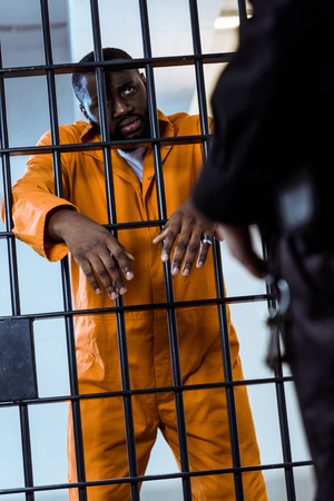 Cropped image of African american prisoner looking at security guard Banco de Imagens