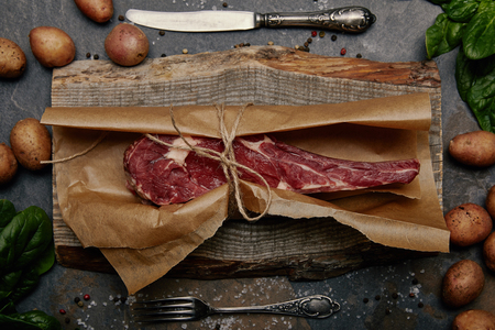 Raw rib eye steak wrapped in baking paper on wooden board with spices, potatoes and kitchen cutlery