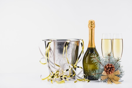 Close up view of bucket with confetti, bottle and glasses of champagne on grey backdrop