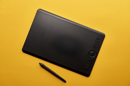 Top view of graphics tablet and pen on yellow surface Imagens