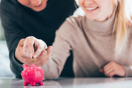 Cropped shot of happy couple putting coin into pink piggy bank Standard-Bild