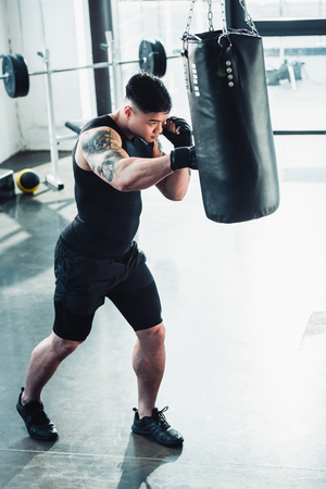 Young sportsman wearing boxing gloves and punching boxing bag at gym