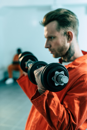 Prisoner training with dumbbells in prison cell Stock Photo