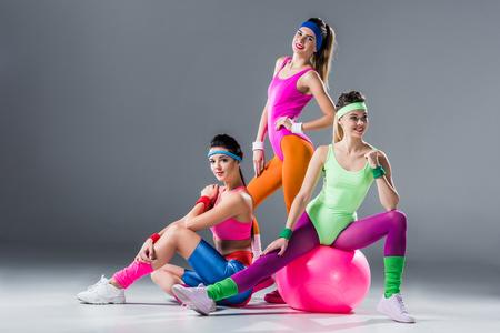Schöne sportliche Frauen in Sportkleidung im Stil der 80er Jahre, die zusammen auf Grau posieren