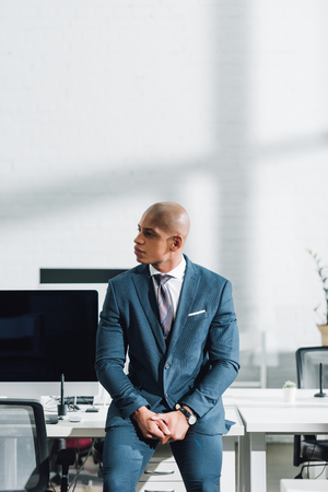 Young African american businessman looking away while sitting in office