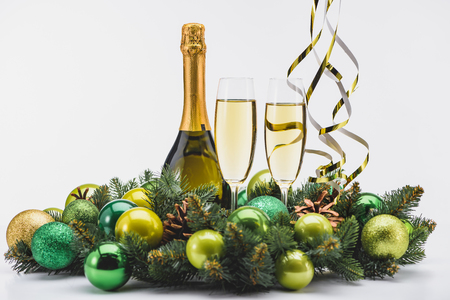 Close up view of bottle and glasses of champagne with Christmas wreath on white background