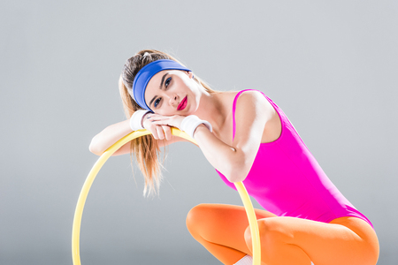 Beautiful young sportswoman leaning at hula hoop and smiling at camera isolated on grey